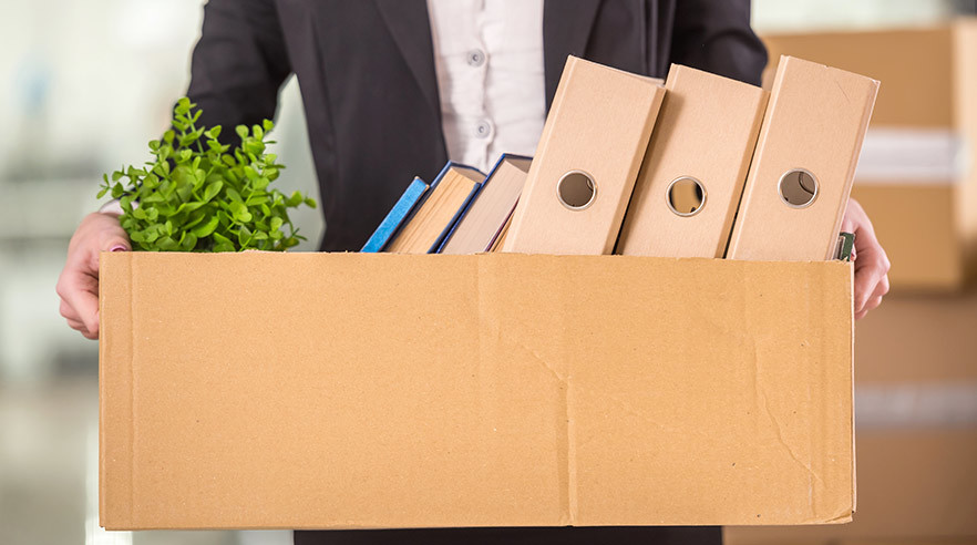 Man holding box of personal possessions after being fired from his job