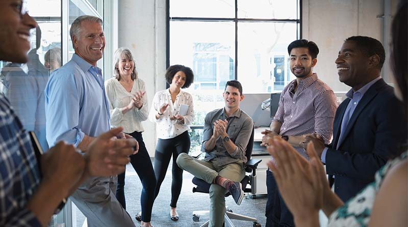 Team members celebrate at a stand-up meeting