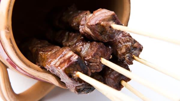 Arrosticini di carne di pecora fatti a mano cotti sulla brace - Il Capestrano, Milano