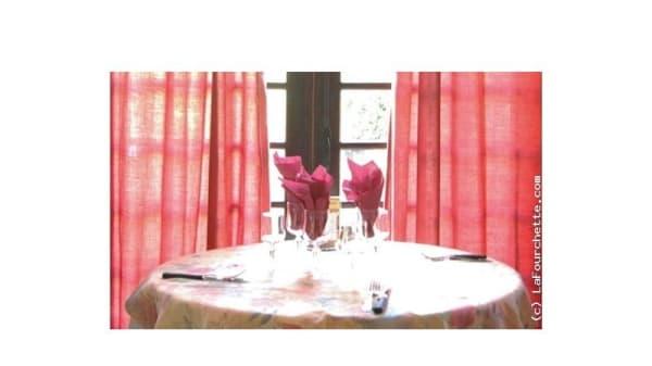 Table ronde et rideaux rouge du restaurant Le Prieuré - Le Prieuré, Maule