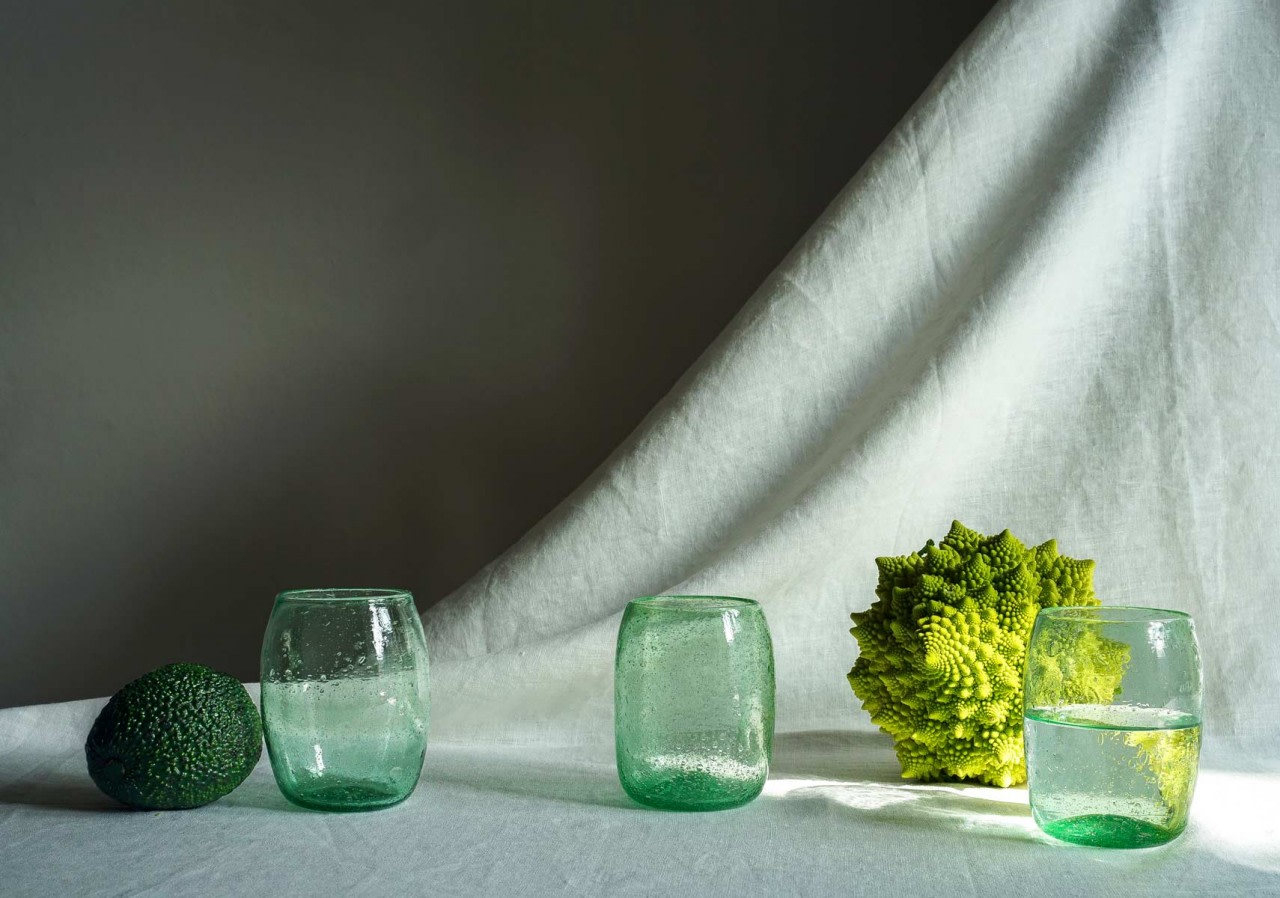 handcrafted tumblers, arranged with green vegetables