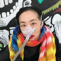 Image description: Color photograph of an Asian American woman in a wheelchair. She is wearing a black jacket with a multi-colored patterned scarf. She is wearing a mask over her nose with a tube for her Bi-Pap machine. Behind her is a wall full of colorful street art.