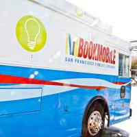 "Blue and white van with the words ""Bookmobile"" across the exterior"