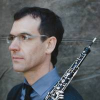 Musician Kyle Bruchmann looks off to the left and holds his oboe