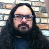 A man with long brown hair and a beard wearing glasses looks at the camera. A brick wall in the background.