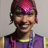 Image description: Sky Cubacub, a non-binary queer and disabled Filipinx human, is wearing colorful chainmail headpiece in magenta, purple, turquoise and yellow. They are wearing a sleeveless purple mesh tank and a necklace that looks like chains in purple and magenta.