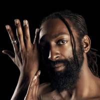 Image features Antoine Hunter, a self-described handsome, dark milk chocolate, African American man. He has long ebony dreadlocks hair tied to back leaving one deadlock on the side of his face, which is close to his eyes. He has a full 1-inch long ebony-colored beard and full brown lips. He is bare-chested and his right hand is to the side of his face with his left hand touching his right forearm. His eyes look straight at you with honest spirit. The background of the image is dark and Antoine is pictured on the right side of the image frame.