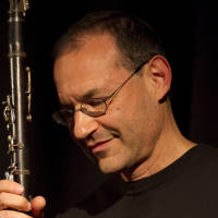 Musician Ben Goldberg looks down and holds his clarinet