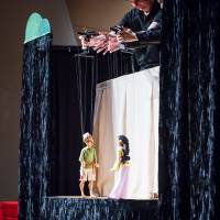 Image of a puppet show with two marionettes in foreground, and the puppeteers hands operating the puppets from above