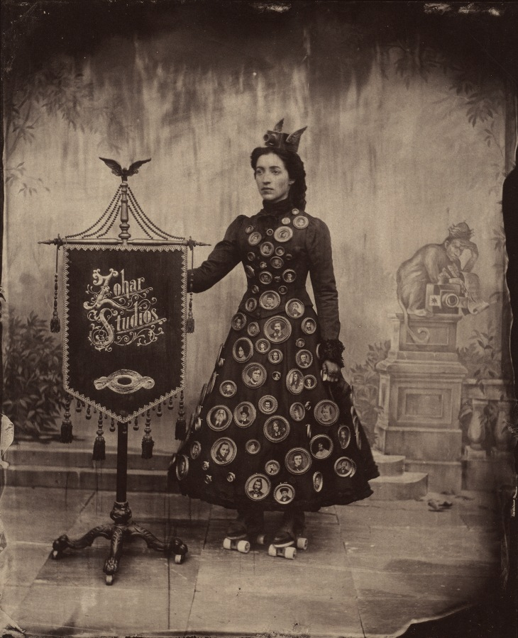 """A sepia-toned photo of a woman standing to the right of a sign embroidered with the words """"Zohar Studios"""""""