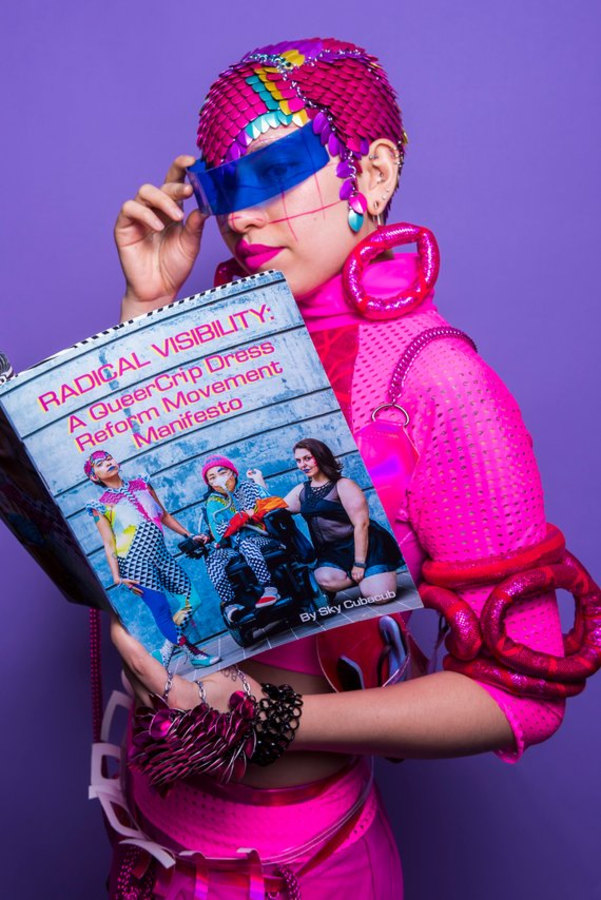 """Image of Sky Cubacub reading the Radical Visibility Manifesto while wearing an all-pink Radical Visibility Collective look which includes a chainmail headpiece in magenta, purple, turquoise, and yellow. They are also wearing large pink fabric hoops on their earsand Vogds blue visor glasses. The cover reads """"Radical Visibility: A QueerCrip Dress Reform Movement Manifesto featuring Sky Cubacub, Alice Wong, and Nina Litoff in Oakland."""