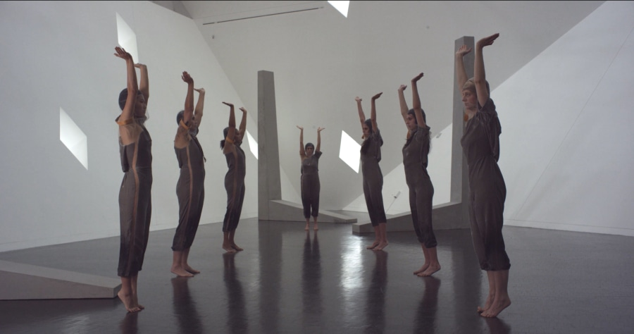 performers standing in the gallery with tall, grey sculptures
