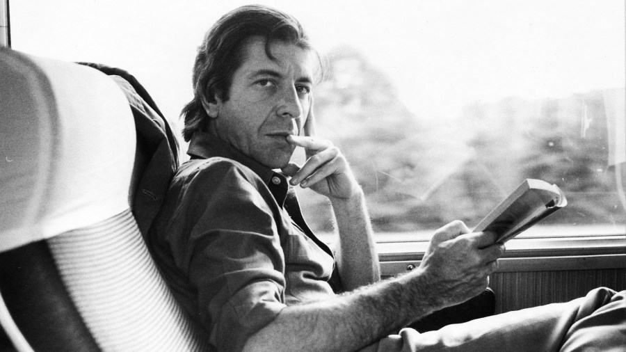A black-and-white photo of Leonard Cohen sitting on a train, holding an open book