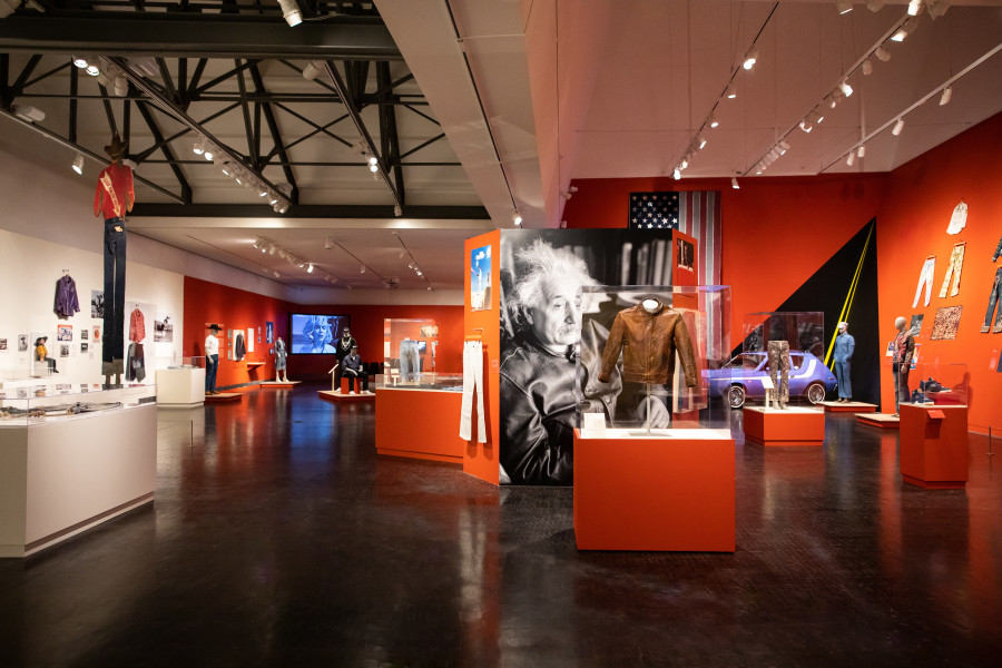 "Installation view of the exhibition ""Levi Strauss: A History of American Style."" There is a photograph of Albert Einstein in the center of the shot, in front of a vitrine with his leather jacket, and several other garments on mannequins in the background."