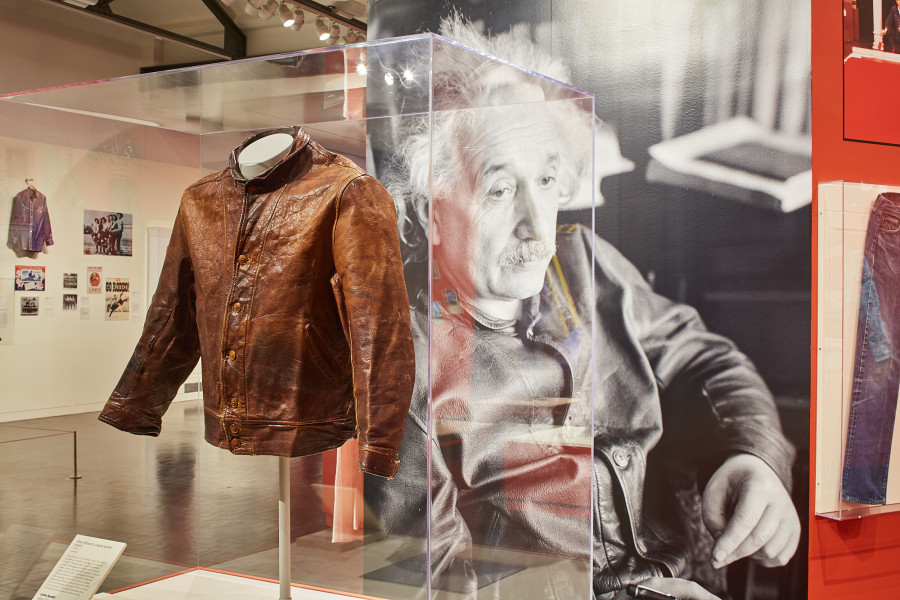 Photo of Albert Einstein's brown leather jacket in the Levi Strauss exhibition, encased in glass. Behind the jacket is a black-and-white photo of Einstein, looking off to the right and wearing the leather jacket.