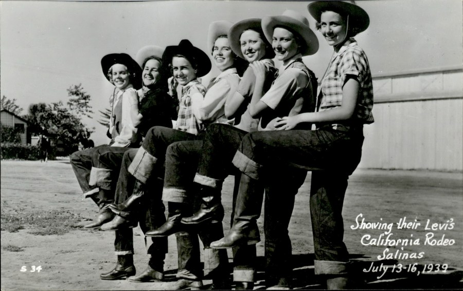Seven women in cowboy hats lined up wearing Levi's jeans