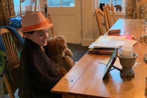 Student wears a hat and shows a teddy bear in meeting on Zoom