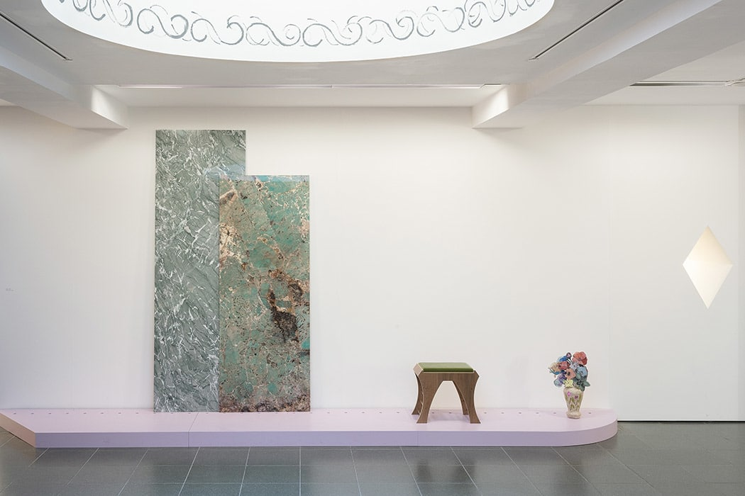This image is an instillation shot of a white room with a lilac platform against the wall. From left to right on the platform are two large marble slabs leaning against the wall, a wooden stool with a green top, and a vase with pink and blue flowers.