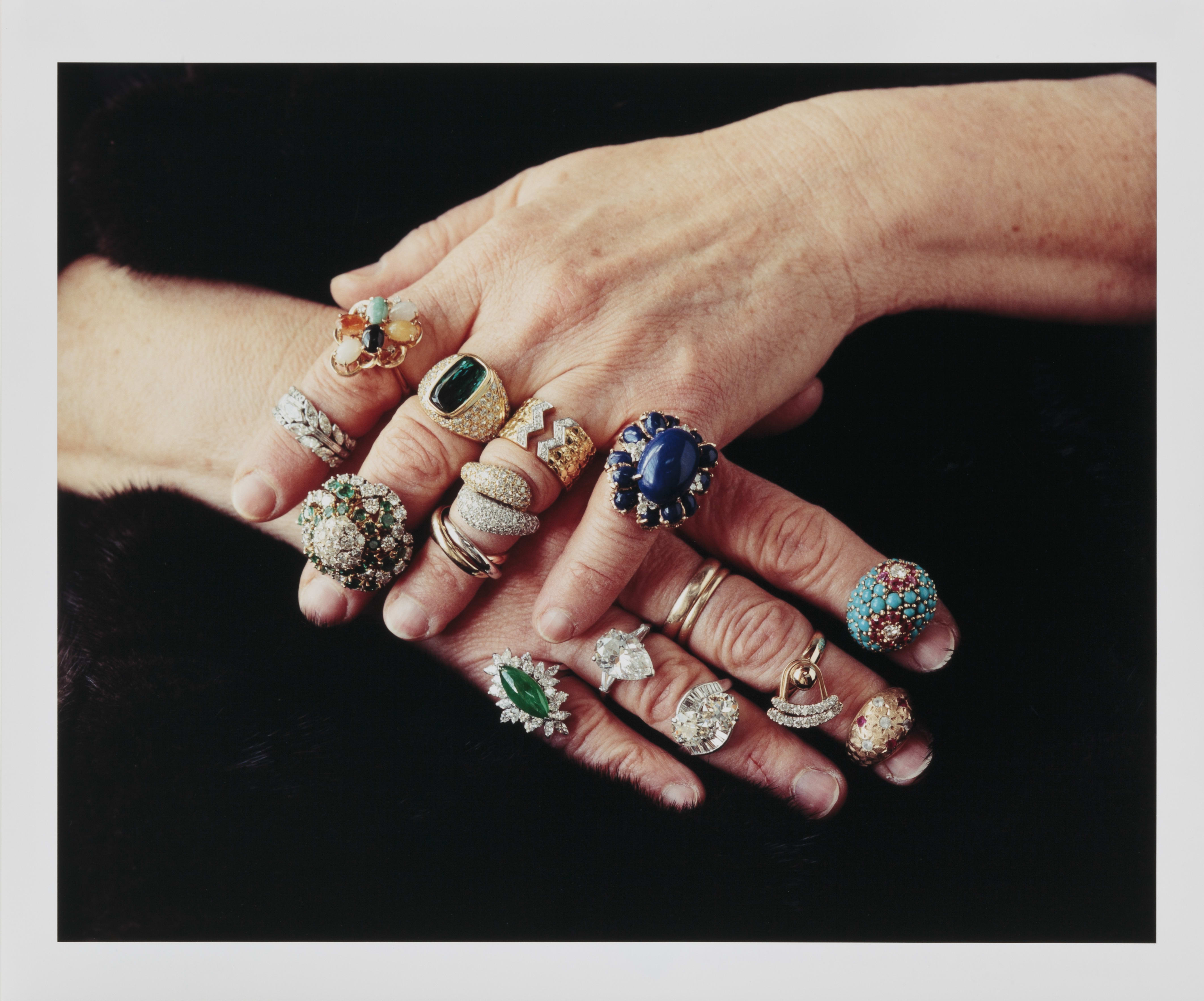 Two light skinned hands rest, calmly touching each other, on a black fur background. Each finger, except for the thumbs, wears one or more jeweled rings, in a mixture of colors and metals.