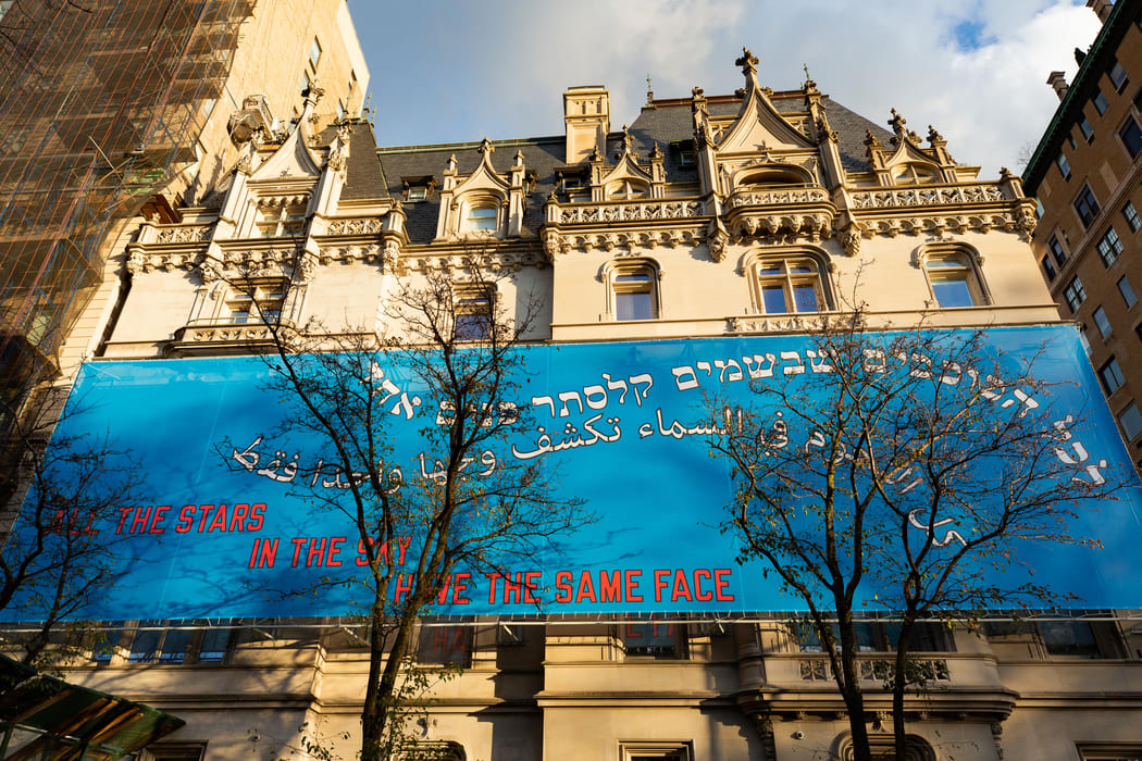 """Alt text: A large blue banner across the Jewish Museum's facade reading """"All the Stars in the Sky Have the Same Face"""" in English, Hebrew, and Arabic. Trees block parts of the banner."""
