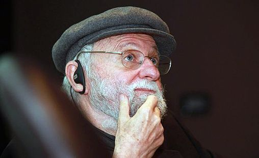 The image is a picture of Don Norman who is the Daddy of UX Design. Don Norman is an older gentleman with glasses and a beard. He looks a little like a fisherman. In this picture he is wearing a flat cap. He is caucasian with white hair.