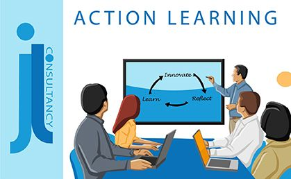 Action Learning. This image contains a group of adults sitting in a classroom environment with the words innovate, learn and reflect written on the board.