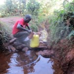 The Water Project: Eluhobe Community, Amadi Spring -  Mr Andrew Nyanje Fetches Water From Amadi Spring