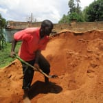 The Water Project: Nyira Community, Ondiek Spring -  Mr Ondiek Works To Load Construction Materials Into Trucks