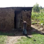 The Water Project: Timbito Community, Wakamu Spring -  A Child Outside His Home