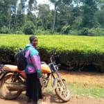 The Water Project: Muleche Primary School -  Field Officer Joan Were Poses Next To A Tea Plantation Opposite The School