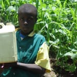 The Water Project: Gemeni Salvation Primary School -  Boy Holds Up Container Filled With Water