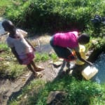 The Water Project: Mukhangu Community, Okumu Spring -  Filling Smaller Container With Water At Spring