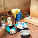 The Water Project: Kegoye Primary School -  Helping Clean Utensils At Plastic Tank