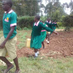 The Water Project: Kigulienyi Primary School -  Carrying Water Back To School
