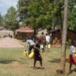 The Water Project: Kigulienyi Primary School -  Students Bringing Water To The Construction Site