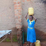 The Water Project: Saride Primary School -  Student Carrying Water