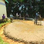 The Water Project: Kapkures Primary School -  Adding Concrete To Rain Tank Foundation