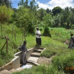 The Water Project: Bukhanga Community, Indangasi Spring -  Community Members Demonstrate Social Distancing While Fetching Water