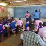 The Water Project: Bulukhombe Primary School -  Pupils Present Work As Patience Records It On Board