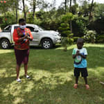 The Water Project: Nyira Community, Ondiek Spring -  Facilitator Takes Elvis Through Handwashing Steps