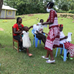 The Water Project: Ematiha Community, Ayubu Spring -  The Facilitator Handing Out The Training Aids