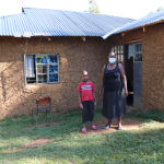 The Water Project: Mukhangu Community, Okumu Spring -  Felistus With Her Son Outside Their Home