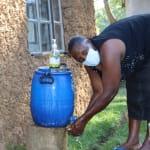The Water Project: Mukhangu Community, Okumu Spring -  Washing Her Hands