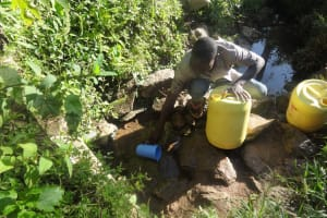 The Water Project: Shitungu Community, Hessein Spring -  Scooping Water