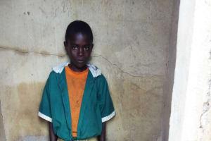 The Water Project: Kalenda Primary School -  Boy Inside Latrine No Shoes
