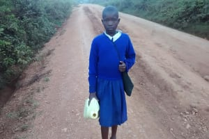The Water Project: Ebusiloli Primary School -  Girl Carrying Water To School