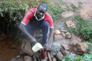 The Water Project: Eluhobe Community, Amadi Spring -  Mr Dickson Makutwa Getting Drinking Water