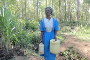 The Water Project: Murumba Community, Muyokani Spring -  Woman Carries Her Jerrycans To The Spring