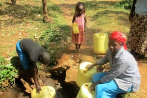 The Water Project: Mutambi Community, Kivumbi Spring -  Fetching Water