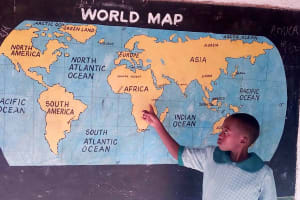 The Water Project: Eshisuru Primary School -  Pupil Shows Position Of Her School On The World Map